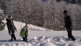 Η ευτυχής νέα οικογένεια έχει το παιχνίδι διασκέδασης στο χιόνι Ρίχνουν το χιόνι και το γέλιο Επίσης χαρούμενα περιέρχονται στο χ απόθεμα βίντεο