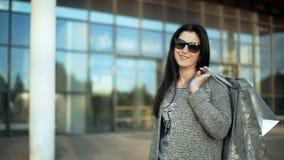 Η ευτυχής νέα τοποθέτηση γυναικών μόδας με τις αγορές τοποθετεί σε σάκκο κοντά στο παράθυρο λεωφόρων απόθεμα βίντεο