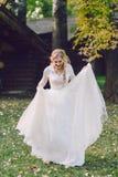 Η ευτυχής νύφη θέτει στο κυματίζοντας φόρεμα στη φύση _ στοκ φωτογραφία με δικαίωμα ελεύθερης χρήσης