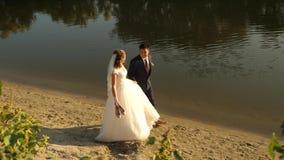 Η ευτυχής νύφη στο άσπρο φόρεμα και ο νεόνυμφος στο κοστούμι περπατούν χωρίς παπούτσια στην άμμο κατά μήκος της άκρης του riverba απόθεμα βίντεο