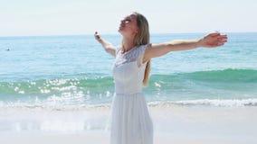 Η ευτυχής ξανθή γυναίκα με τα όπλα στην παραλία απόθεμα βίντεο