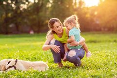 Η ευτυχής οικογένεια έχει τη διασκέδαση με χρυσό retriever - μητέρα και αυτός στοκ φωτογραφίες με δικαίωμα ελεύθερης χρήσης