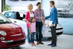 Η ευτυχής οικογένεια αγοράζει το νέο αυτοκίνητο Στοκ εικόνες με δικαίωμα ελεύθερης χρήσης