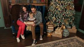 Η ευτυχής οικογένεια ανοίγει τα δώρα κοντά στο χριστουγεννιάτικο δέντρο απόθεμα βίντεο