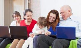Η ευτυχής οικογένεια απολαμβάνει στον καναπέ με λίγα lap-top Στοκ φωτογραφία με δικαίωμα ελεύθερης χρήσης