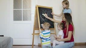 Η ευτυχής οικογένεια επισύρει την προσοχή με τα κραγιόνια στον πίνακα στο σπίτι απόθεμα βίντεο