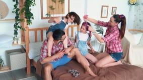 Η ευτυχής οικογένεια με δύο κόρες στηρίζεται στην κρεβατοκάμαρα, το παιχνίδι και το γέλιο, σε αργή κίνηση απόθεμα βίντεο