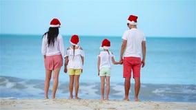 Η ευτυχής οικογένεια με δύο παιδιά στο καπέλο Santa στις θερινές διακοπές γιορτάζει τα Χριστούγεννα φιλμ μικρού μήκους
