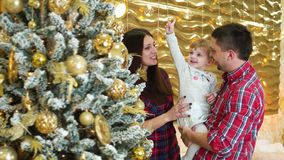 Η ευτυχής οικογένεια με λίγη κόρη διακόσμησε πλησίον το χριστουγεννιάτικο δέντρο στο σπίτι φιλμ μικρού μήκους