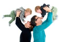 Η ευτυχής οικογένεια με τα υιοθετημένα δίδυμα γελά Απομονωμένος στο λευκό στοκ εικόνες