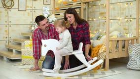 Η ευτυχής οικογένεια με την κόρη μικρών παιδιών στο άλογο λικνίσματος γιορτάζει τα Χριστούγεννα απόθεμα βίντεο