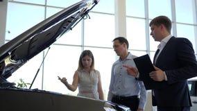 Η ευτυχής οικογένεια με τον έμπορο αυτοκινήτων στο αυτόματο κατάστημα, άτομο φαίνεται μηχανή μηχανών, ο σύζυγος και η σύζυγος επι απόθεμα βίντεο