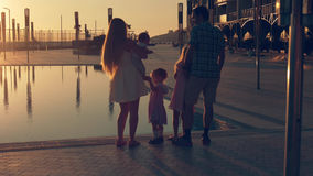 Η ευτυχής οικογένεια με τρία παιδιά που θαυμάζουν το ηλιοβασίλεμα απεικόνισε στην επιφάνεια της λίμνης στοκ εικόνα