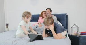 Η ευτυχής οικογένεια ξοδεύει το χρόνο προσέχοντας μαζί το βίντεο στον ψηφιακό υπολογιστή ταμπλετών στα παιδιά κρεβατοκάμαρων με τ απόθεμα βίντεο