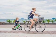 Η ευτυχής οικογένεια οδηγά τα ποδήλατα υπαίθρια και χαμογελά Mom σε ένα ποδήλατο Στοκ Φωτογραφίες