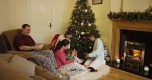 Η ευτυχής οικογένεια πέντε κάθεται κοντά στο χριστουγεννιάτικο δέντρο και εξετάζει τα δώρα στο σπίτι, το κορίτσι δίνει ένα δώρο σ φιλμ μικρού μήκους