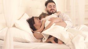 Η ευτυχής οικογένεια που βρίσκεται στο κρεβάτι μαζί και το μικρό κορίτσι ξυπνά φιλμ μικρού μήκους