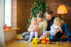 Η ευτυχής οικογένεια που δίνει η μια την άλλη παρουσιάζει στο πρωί Χριστουγέννων στοκ εικόνες με δικαίωμα ελεύθερης χρήσης