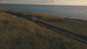 Η ευτυχής οικογένεια που τρέχει κατά μήκος της ακτής και έχει τη διασκέδαση, πυροβολώντας από τον αέρα απόθεμα βίντεο