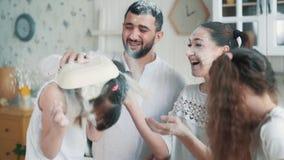 Η ευτυχής οικογένεια ρίχνει το αλεύρι ο ένας στον άλλο, έχει το χρόνο διασκέδασης στην κουζίνα, σε αργή κίνηση φιλμ μικρού μήκους