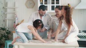 Η ευτυχής οικογένεια ρίχνει το αλεύρι ο ένας στον άλλο, έχει το χρόνο διασκέδασης στην κουζίνα, σε αργή κίνηση απόθεμα βίντεο