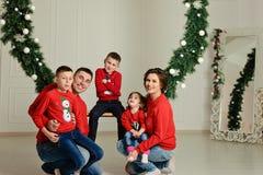 Η ευτυχής οικογένεια στα ίδια πουλόβερ κάθεται σε μια ταλάντευση το χειμώνα στη μέση των διακοπών Χριστουγέννων στοκ εικόνες