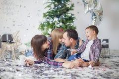 Η ευτυχής οικογένεια στα ελεγμένα πουκάμισα χαίρεται για το νέο έτος, χριστουγεννιάτικο δέντρο, δώρα στοκ φωτογραφίες με δικαίωμα ελεύθερης χρήσης
