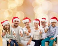 Η ευτυχής οικογένεια στην παρουσίαση καπέλων santa φυλλομετρεί επάνω Στοκ φωτογραφία με δικαίωμα ελεύθερης χρήσης