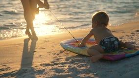 Η ευτυχής οικογένεια στη θάλασσα κολυμπά η μητέρα και το παιδί που παίζουν μια διασκέδαση σπάζουν από την πόλη στο θαλάσσιο νερό  απόθεμα βίντεο