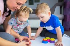 Η ευτυχής οικογένεια των διδύμων μητέρων και μικρών παιδιών χρωματίζει Στοκ εικόνες με δικαίωμα ελεύθερης χρήσης