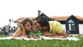 Η ευτυχής οικογένεια υπαίθρια στη χλόη σε ένα πάρκο, χαμόγελο αντιμετωπίζει όλο το ξάπλωμα έχοντας τη διασκέδαση φιλμ μικρού μήκους