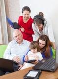 Η ευτυχής οικογένεια χρησιμοποιεί λίγες ηλεκτρονικές συσκευές Στοκ φωτογραφία με δικαίωμα ελεύθερης χρήσης