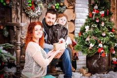 Η ευτυχής οικογένεια Χριστουγέννων τριών ατόμων και δέντρου έλατου με το νέο χειμώνα έτους κιβωτίων δώρων διακόσμησε το υπόβαθρο Στοκ Φωτογραφίες