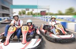 Η ευτυχής οικογενειακή οδήγηση πηγαίνει kart στη διαδρομή στοκ εικόνα