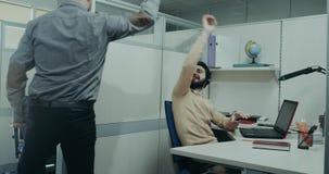 Η ευτυχής ομάδα που εργάζεται στο τηλεφωνικό κέντρο, ένας από τους εργαζομένους που περπατούν πίσω από τους και που δίνουν πέντε, απόθεμα βίντεο
