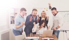 Η ευτυχής ομάδα επιχειρηματιών γιορτάζει την επιτυχία στο γραφείο Στοκ φωτογραφία με δικαίωμα ελεύθερης χρήσης