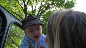 Η ευτυχής παιδική ηλικία, γυναίκα υψηλή ανυψώνει το λατρευτό μωρό της στο backlight στην κίνηση στα δέντρα υποβάθρου φιλμ μικρού μήκους