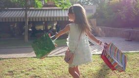 Η ευτυχής παιδική ηλικία, χαμογελώντας κορίτσι που απολαμβάνει τις νέες αγορές στις τσάντες εγγράφου και περιστρέφεται στην πράσι απόθεμα βίντεο