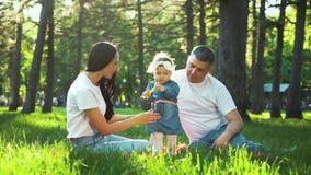 Η ευτυχής παραδοσιακή οικογένεια με το μικρό κορίτσι ξοδεύει το χρόνο μαζί στο ηλιόλουστο πάρκο φιλμ μικρού μήκους