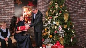 Η ευτυχής παραμονή οικογενειακού νέα έτους ` s, σύζυγος δίνει τα δώρα στη σύζυγο και στα παιδιά του, μια γιορτή Χριστουγέννων στη απόθεμα βίντεο