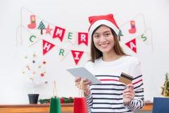 Η ευτυχής πιστωτική κάρτα χρήσης γυναικών της Ασίας αγοράζει το δώρο Χριστουγέννων με κινητό Στοκ Φωτογραφίες