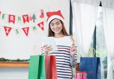 Η ευτυχής πιστωτική κάρτα χρήσης γυναικών της Ασίας αγοράζει το δώρο Χριστουγέννων με κινητό Στοκ Εικόνες