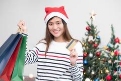 Η ευτυχής πιστωτική κάρτα χρήσης γυναικών της Ασίας αγοράζει το δώρο Χριστουγέννων στις αγορές Στοκ φωτογραφία με δικαίωμα ελεύθερης χρήσης