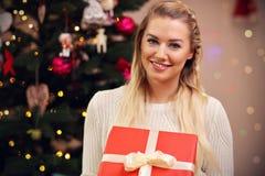 Η ευτυχής τοποθέτηση γυναικών με παρουσιάζει κατά τη διάρκεια του χρόνου Χριστουγέννων στοκ φωτογραφία