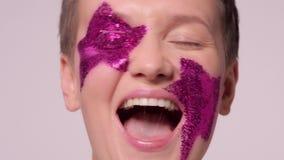 Η ευτυχής τραγουδώντας γυναίκα με ακτινοβολεί αστέρια makeup φιλμ μικρού μήκους