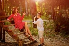 Η ευτυχής φυσώντας πικραλίδα παιδιών υπαίθρια την άνοιξη σταθμεύει Στοκ Φωτογραφία