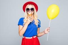Η ευτυχής χαμογελώντας γυναίκα μόδας με το κίτρινο μπαλόνι αέρα και ο κώνος παγωτού που φορά το καπέλο αχύρου και το χρώμα ντύνου Στοκ Εικόνες