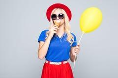 Η ευτυχής χαμογελώντας γυναίκα μόδας με το κίτρινο μπαλόνι αέρα και ο κώνος παγωτού που φορά το καπέλο αχύρου και το χρώμα ντύνου Στοκ εικόνες με δικαίωμα ελεύθερης χρήσης