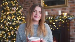 Η ευτυχής χαμογελώντας γυναίκα στο πουλόβερ πίνει την καυτή σοκολάτα κοντά στο λάμποντας χριστουγεννιάτικο δέντρο στο καθιστικό τ απόθεμα βίντεο