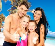 Η ευτυχής χαμογελώντας οικογένεια με τους αντίχειρες υπογράφει επάνω Στοκ Εικόνα